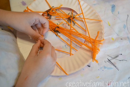 Grab a paper plate and some yarn to weave your own web with this fun and spooky Spider Web Wreath kids Halloween craft this October.