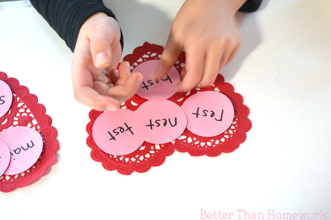 Get out paper doilies to help practice word families with a fun Valentine Word Family Game. It's a fun Valentine reading game.